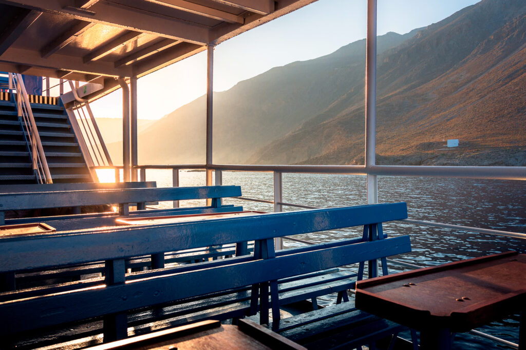 Gorgeous sunset from the deck of a ship, as it approaches the greek village of Loutro, Chania, Crete, Greece.