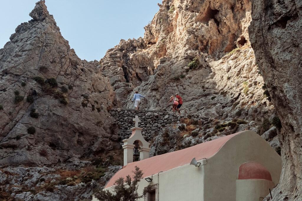 Kourtaliotiko gorge. Small church of St. Nicholas. Tourists climbing up. Crete, Greece