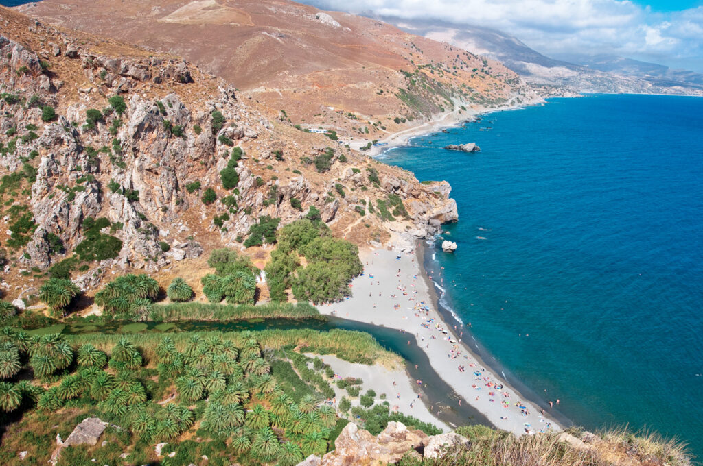 Aerial view of Preveli beach and lagoon full of people in Crete, Greece.