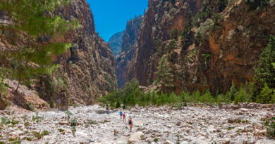 The famous Samaria Gorge in the White Mountains on the island of Crete in Greece. Tourists walking along the hiking trail ahead crossing the dry riverbed.