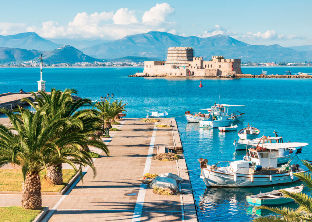 Beautiful port of Nafplio city with small boats, palm trees and Bourtzi castle on the water, Greece