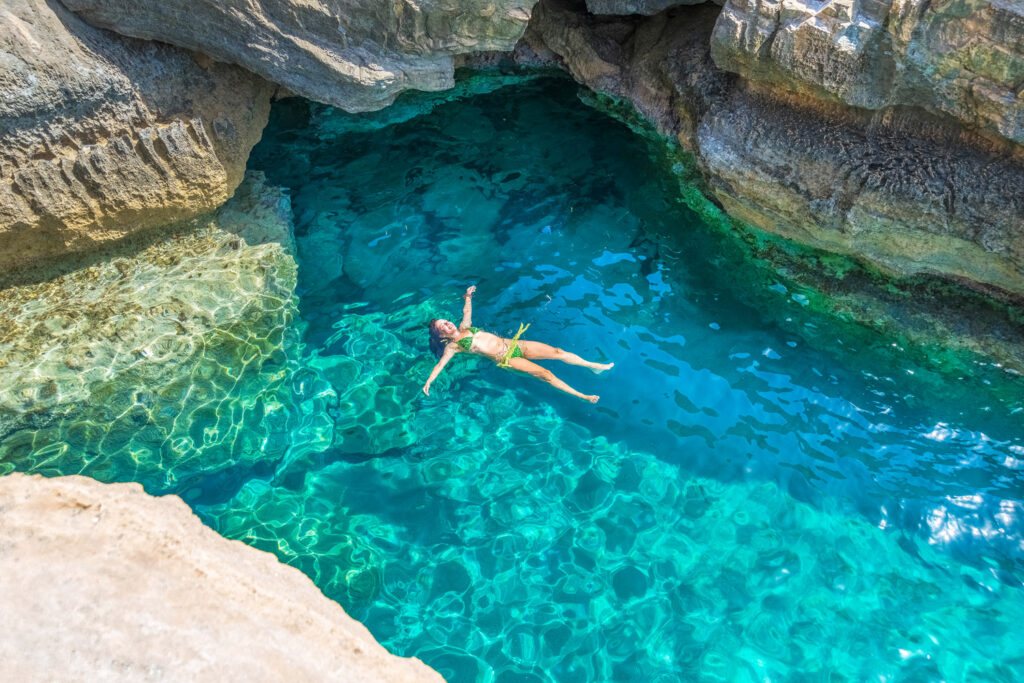 Young woman swimming between the rocks of Preveli beach in Crete, Greece. Crystal clear blue water and scenery like a lagoon.