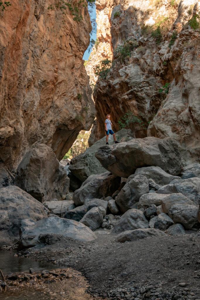 Man standing on a big rock and looking around in deep canyon, Sarakinas Gorge, Crete, Greece
