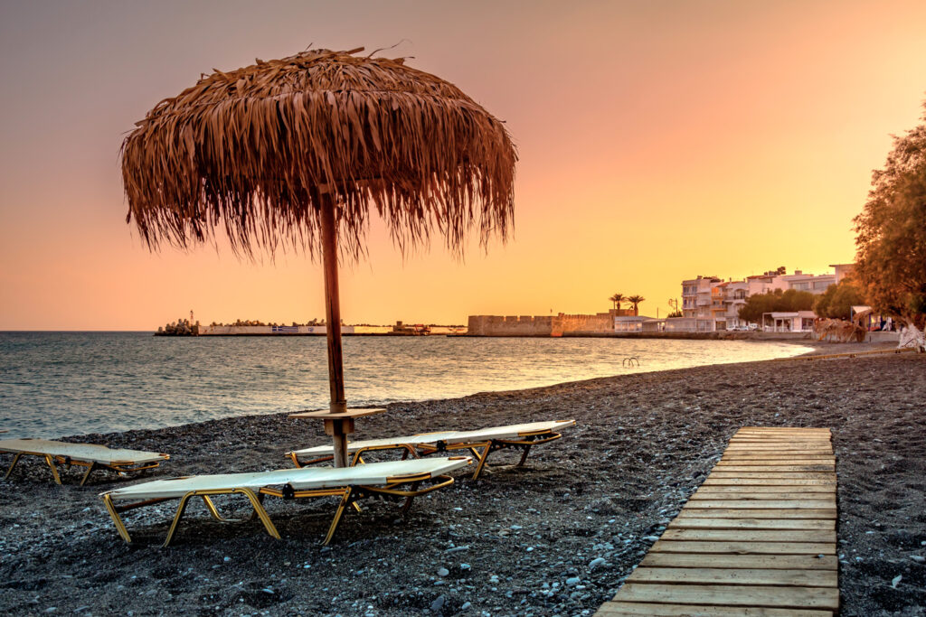 View of the beach in Ierapetra at sunset with the Kales Venetian fortress at the entrance to the harbour, Ierapetra, Crete, Greece