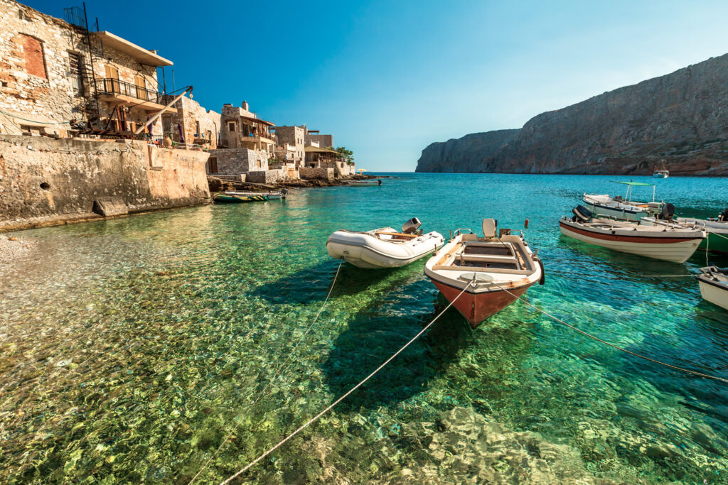 Boats in the crystal-clear waters of Gerolimenas in Mani peninsula, Peloponnese Greece
