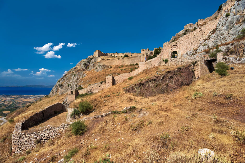 Acrocorinth (the acropolis of ancient Corinth) - fortified citadel formed on the top of monolithic rock. There is the Corinthian Gulf in the background, Greece
