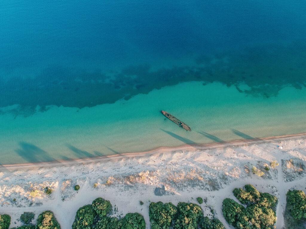 Aerial view of a shipwreck at Gialova beach near Pylos. Natural scenery of an abandoned sunken ship in Navarino bay near Voidokilia, Messinia, Greece