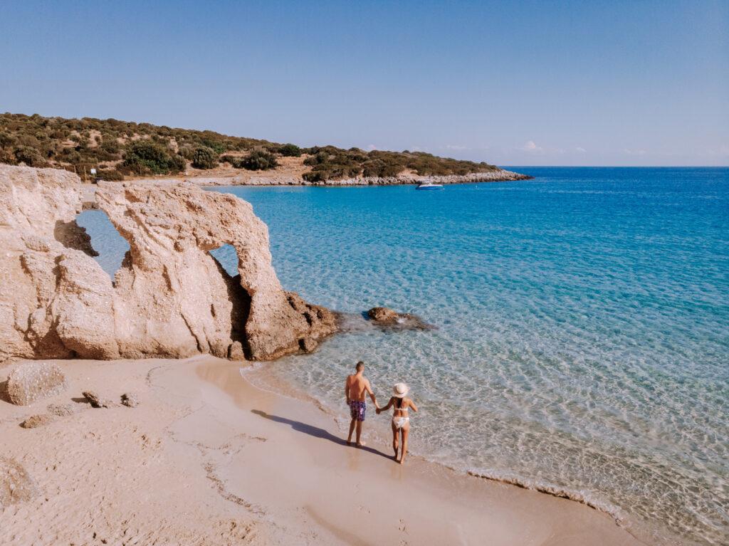 Tropical Voulisma beach, Istron, Crete, Greece, som of the most beautiful beaches of Crete -Istron Bay near Agios Nikolaos drone aerial view, couple walking on the beach