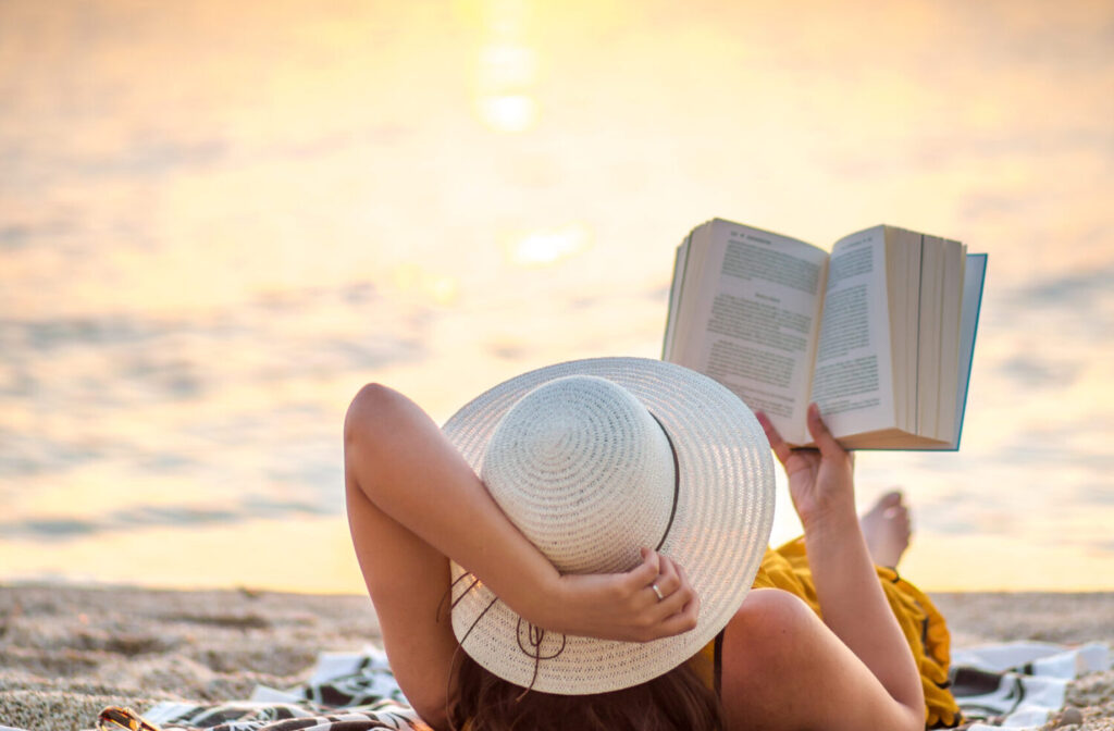 Young woman reading a book at the beach while the sun rise, Hersonissos, Crete Greece