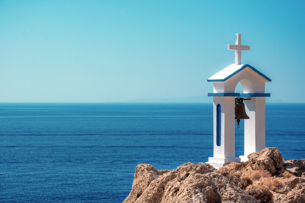 White bell tower of a church beside blue sea, at a sunny day, Loutro, Chania, Crete, Greece